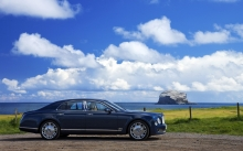 Взгляд сбоку на синий Bentley Mulsanne напротив морского горизонта